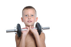 Young boy lifting a very heavy dumbbell Royalty Free Stock Image