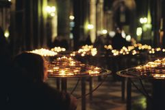 Young boy lighting candles in church. Surrounded by lit candles Stock Photos