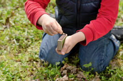 Young boy lighting a fire outdoors. Kneeling down in the grass striking a match against the box Royalty Free Stock Photography