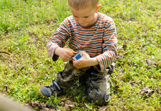 Young boy lighting a fire outdoors. Kneeling down in the grass striking a match against the box Stock Photos