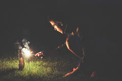 Young boy lighting fireworks