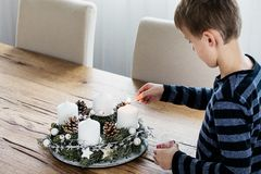 Young boy lighting the first candle on Advent Wreath royalty free stock photo