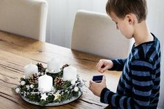 Young boy lighting the first candle on Advent Wreath stock image
