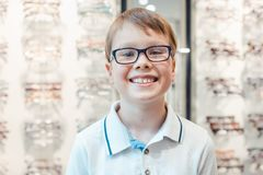 Young boy liking the new glasses he has got from the optician. Smiling royalty free stock images