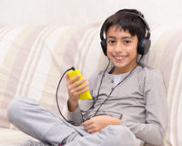Young boy listening music  headphone. Young boy listening music with smart phone and headphone Royalty Free Stock Photography