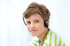 Young boy listening music on headphones Stock Photo