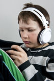 Boy with earphones. Young boy listening to music in earphones wile playing or texting on a cellphone Royalty Free Stock Photos