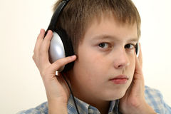 Young boy is listening to the music with headphone stock images
