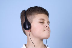 Young boy listening to music on headphones. Head shot of a young boy enjoying music on headphones with a blue background Royalty Free Stock Photo