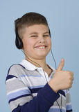 Young boy listening to music on headphones. Young boy enjoying music on headphones giving the thumbs up signal. Blue background stock photos