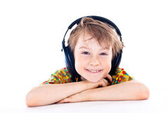 Young boy listening to music on headphones. Portrait of a sweet young boy listening to music on headphones against white background stock photo