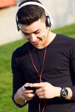 Young boy  listening to music with  smartphone in the street Stock Image