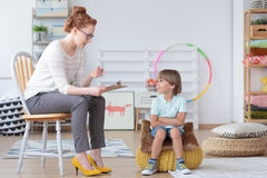 Young boy listening to psychotherapist Stock Photo