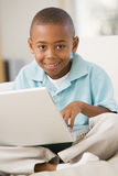 Young boy in living room with laptop Stock Photos