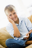 Young boy in living room with MP3 player Royalty Free Stock Image