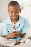 Young boy in living room using cellular phone Stock Image