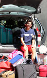 Young boy loads the car with a lot of luggage before leaving for Stock Image