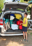 Young boy loads the luggage in the trunk of his car. Young boy loads his luggage in the trunk of the car during the trip of the summer holidays Royalty Free Stock Images