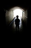 Young boy in long tunnel walkway Royalty Free Stock Photo