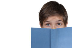 Young boy looking through behind a blue book. Isolated on white Royalty Free Stock Images