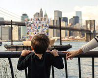Young boy looking at boat with Manhattan skyline at background Royalty Free Stock Photo