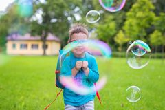 Young boy looking through a bubble smiling. Summer. Outdoor. Green lawn Stock Image