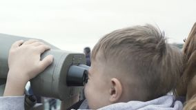 Young boy looking city panorama by tourist binoculars on Victoria Peak Hong Kong China. Tourist boy together mother. Looking telescope on observation deck stock video footage