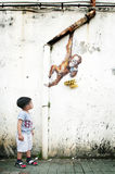 Young boy looking Ernest Zacharevic wall mural Royalty Free Stock Photography