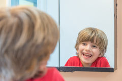 Young boy looking at himself in mirror Stock Photos