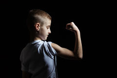 Young Boy Looking at his Strong Biceps on Black Royalty Free Stock Images