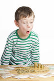 Young boy is looking at a lot of money Royalty Free Stock Image