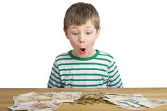 Young boy is looking at a lot of money Stock Images