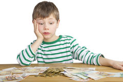 Young boy is looking at a lot of money. Young boy is looking amazed at a lot of money Royalty Free Stock Images