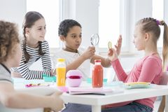 A young boy looking through a magnifying glass and a girl holding a slice of cucumber while other kids are watching during stock photos