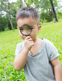 Young boy looking through magnifying glass stock images