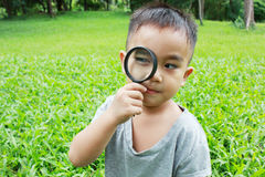 Young boy looking through magnifying glass royalty free stock photo