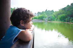 Young boy looking out across lake Royalty Free Stock Photos