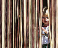 Young boy looking out from behind curtain stock images