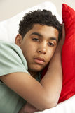 Young Boy Looking Sad On Sofa royalty free stock images