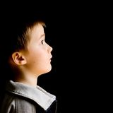 Young boy looking up. Black background Stock Photos
