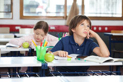 Young Boy Looking Up In Classroom. Thoughtful young boy looking up with girl in background at classroom Royalty Free Stock Photo
