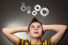 Young boy looking up at Gear Wheel. Student wfith brainstorming Stock Photography