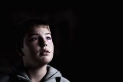 Young boy looking up with hope in his eyes Low key stock photography