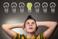 Young boy looking up at light idea bulb. Above head Royalty Free Stock Images