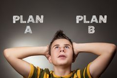 Young boy looking up at plan a and plan b. Young boy looking up at plan a and b Royalty Free Stock Photography