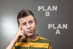 Young boy looking up at plan a and plan b. In background Royalty Free Stock Photos