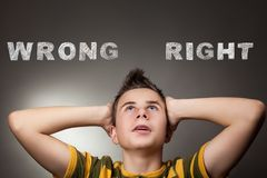 Young boy looking up at wrong and right. Words Stock Photo