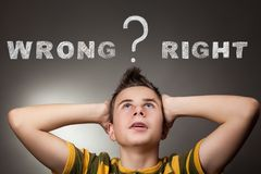 Young boy looking up at wrong and right words. And question sign Royalty Free Stock Image