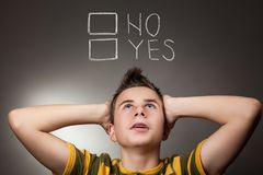 Young boy looking up at Yes and No. Words Stock Images