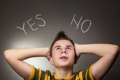 Young boy looking up at Yes and No. Words Stock Image